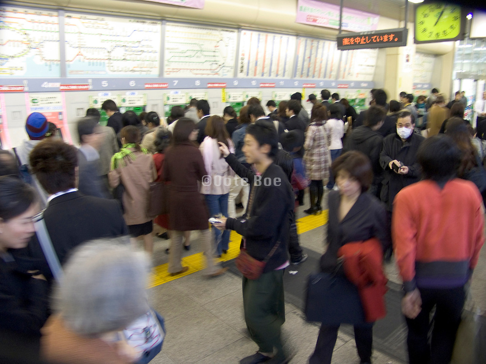 Rush hour crowds buying subway ticket at Tokyo s train stations