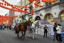 © Licensed to London News Pictures. 24/01/2020. LONDON, UK. Police ride by on horses as red lanterns decorate Chinatown ahead of Chinese New Year, the Year of the Rat.   Photo credit: Stephen Chung/LNP