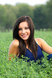 Pretty brunette girl modeling at a farm, in the fields, and near the buildings