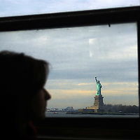 Woman looks at the Statue of Liberty, from her window of the Staten Island Ferry.