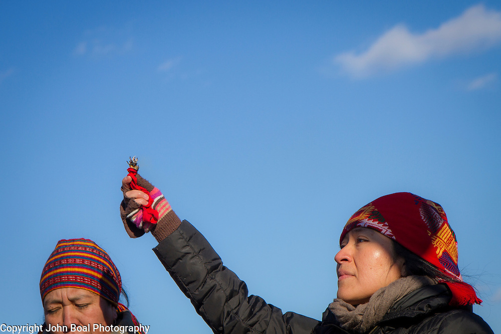 Juanita Cabrera Lopez, holds up burning sage, as Lola Juan, speaks a Mayan prayer, during a protest and march from in front of the U.S. Capitol to the EPA, about the North Dakota Access Pipeline, as well as the effort to free Leonard Peltier.  Saturday, December 10, 2016. John Boal Photography