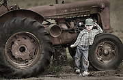 Young boy leaning on antique tractor.