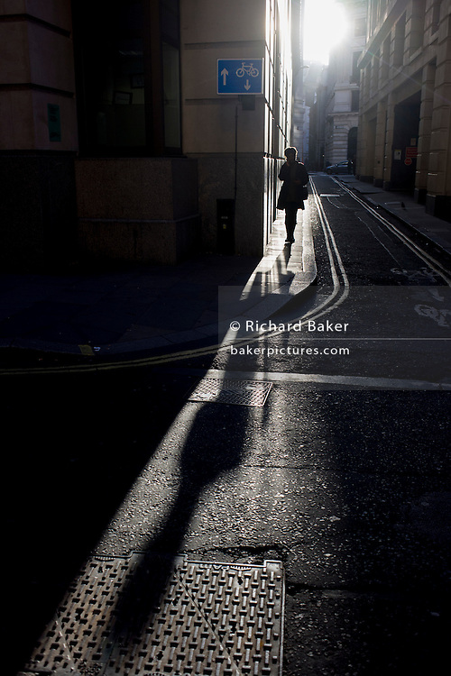A lone woman walks through winter sunlight near the corner of Lombard Street and Abchurch Lane, EC4, in the City of London.