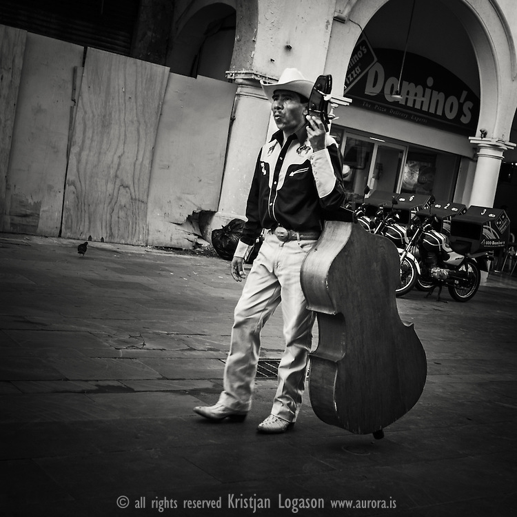 Bass player from a mariachi band walking down a street in Veracruz Mexico