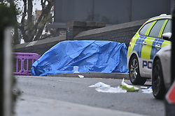 © Licensed to London News Pictures. 24/11/2019. London, UK. A body covered by tarpaulin at the scene where a man has been found stabbed to death outside a west London train station in what is being reported as a road rage incident. The attack follows a stabbing in Whitechapel on Saturday, in which another man in his 20s was killed. Photo credit: Ben Cawthra/LNP