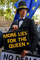 © Licensed to London News Pictures. 04/09/2019. London, UK. Impersonator Charlie Rome, 35 from Charlton dressed as Jacob Rees-Mogg holds a briefcase inscribed with  'More Lies for the Queen' referencing the controversial prorogation of Parliament. Photo credit: Guilhem Baker/LNP