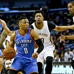 Feb 25, 2016; New Orleans, LA, USA; Oklahoma City Thunder guard Russell Westbrook (0) drives past New Orleans Pelicans forward Anthony Davis (23) and center Alexis Ajinca (42) during the first quarter of a game at Smoothie King Center. Mandatory Credit: Derick E. Hingle-USA TODAY Sports
