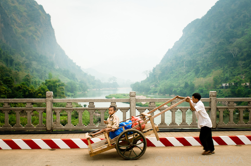 Laos, Nong Khiaw. Man with a cart crossing the bridge.