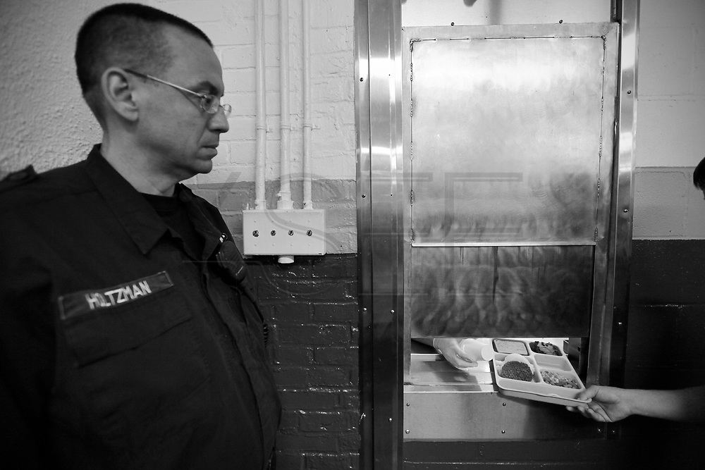 Officer Holtzman looks on as an inmate picks up his lunch.  The Bristol County Jail & House of Correction located on Ash Street in New Bedford, Massachusetts was started in 1829, and is the oldest running jail in the United States.   The Ash street jail, as it is known, has been a controversial facility since it opened.  It is believed to be the site of the last pubic hanging in Massachusetts sometime in the 1890's.  Two big riots broke out in the 90's (1993, 1998) and since then the facility has been modified to alleviate some of the crowded conditions that resulted in the riots.