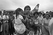 1983-15-08.15th August 1983.15-08-1983.08-15-83..Photographed at Dublin Airport..Family Affair:..Gold medalist Eamonn Coughlan geeeted by press and supporters on the tarmac of Dublin Airport on his return from the World Athletic Championships in Finland. His wife Yvonne and chldren Suzanne (four) and Eamonn Jn (two) are with him. Suzanne is in his arms while his wife holds Eamonn Jn. His mother Kathleen looks on..