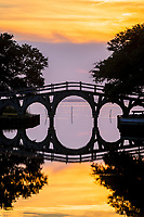 A still sunset reflection of the wooden bridge between the Whale Head Club and Currituck Beach Lighthouse in Corolla on the Outer Banks of NC.