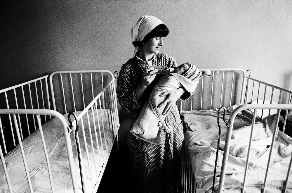 A Baby swaddled tightly in blankets is bottle fed at the Maternity Unit at Bucharest Hospital. Romania Feb 1990
