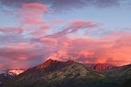 Alpenglow at sunset on Eagle Peak and Hurdygurdy Mountain in Chugach State Park near Eagle River in Southcentral Alaska. Summer. Evening.