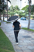 A woman walking through Waikiki with an umbrella.