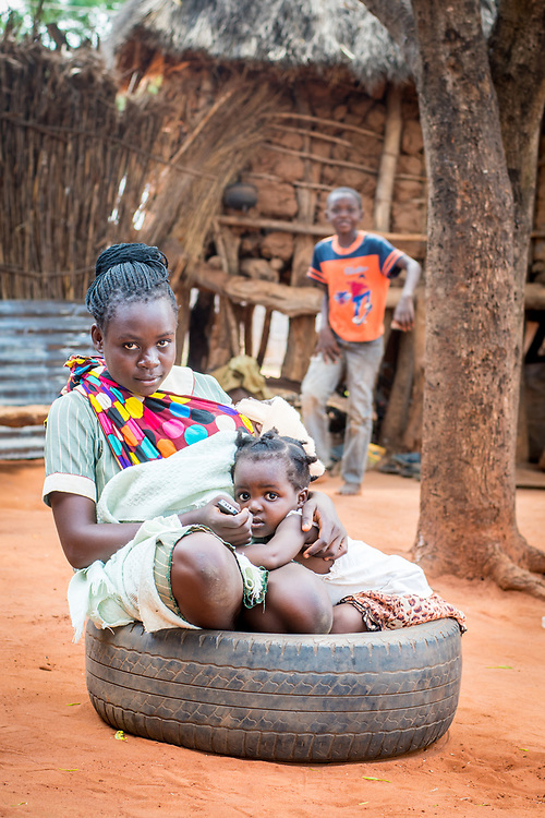 Young Zambian mother sits in tire with her toddler by her side and baby in sling, Mukuni Village, Zambia