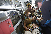 Firefighter and paramedic helping woman in ambulance