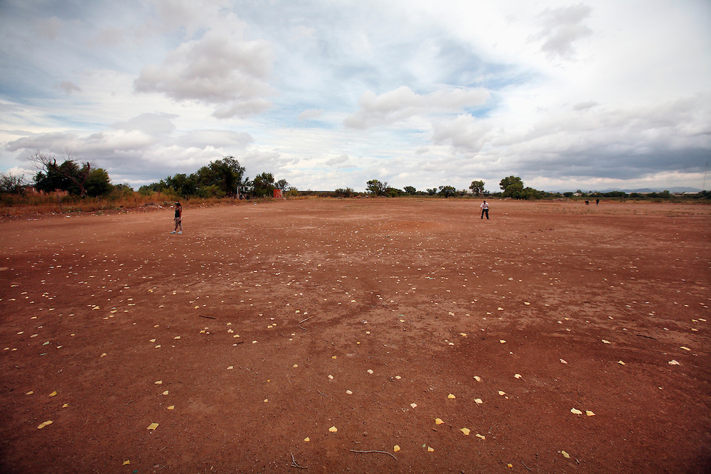 leaves blow across a baseball field under cloudy skies in Agua Perieta, Mexico.