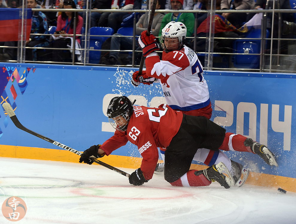 Feb 15, 2014; Sochi, RUSSIA; Switzerland forward Anja Stiefel (63) and Russia defenseman Inna Dyubanok (77) collide in a women's quarterfinals ice hockey game during the Sochi 2014 Olympic Winter Games at Shayba Arena.