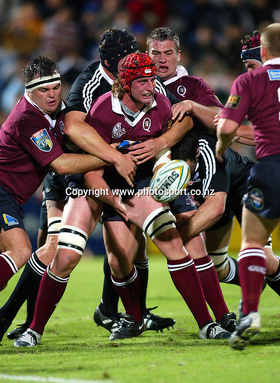 Queenslands Rudi Vedalago trys to get his pass away during the Rugby Union match between Queensland  and the Junior All Blacks at Ballymore, Brisbane on 22 June 2005. The Junior All Blacks won the game 48-15. Photo: Seiser Photography/PHOTOSPORT<br /> <br /> <br /> 127823