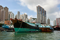 Fishing boats moored in Aberdeen fishing village with high-rise apartment blocks behind Hong Kong Hong Kong August 2008