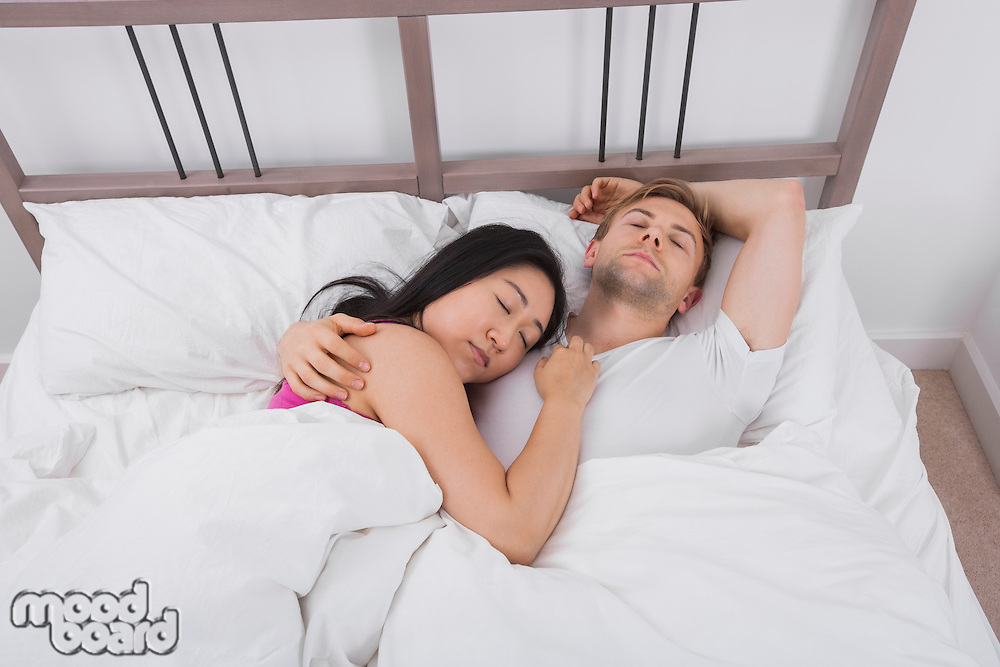 Multiethnic couple sleeping in bed