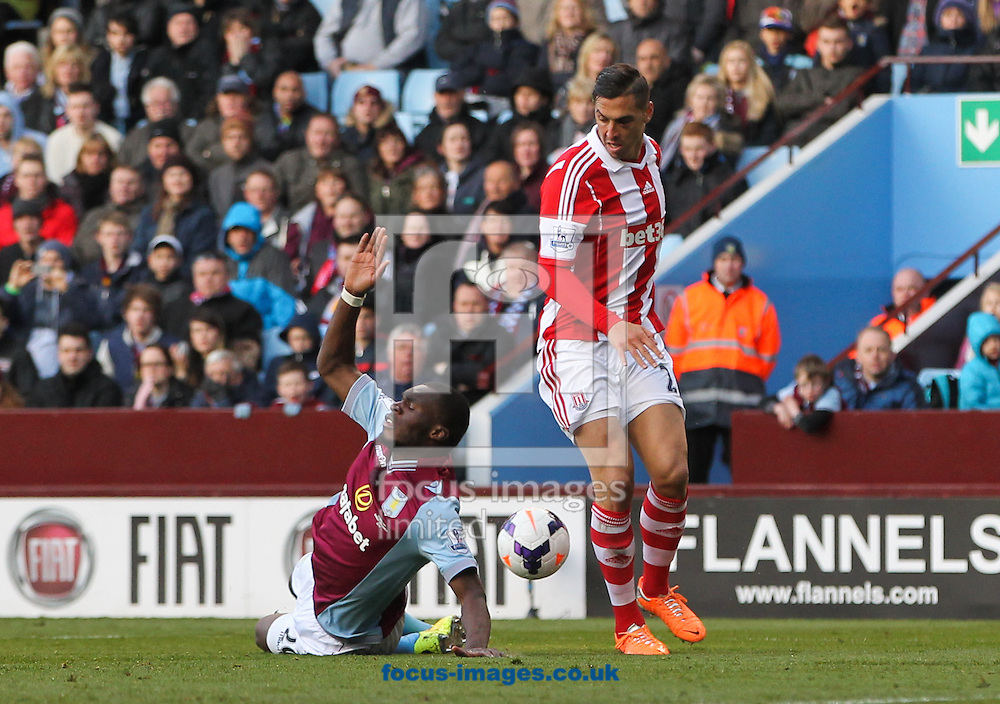 Christian Benteke (left) of Aston Villa goes down in the box during the Barclays Premier League match at Villa Park, Birmingham<br /> Picture by Tom Smith/Focus Images Ltd 07545141164<br /> 23/03/2014