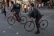 Two identical businessmen in grey suits ride matching bikes, pedalling through rush-hour traffic at London Bridge in Southwark, south London.