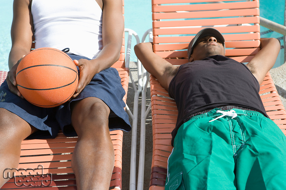 Two Young Man Relaxing on Sunlounger, One with Basketball