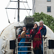 First Nation woman Kiera Dawn-Kolson speakes to the crowd from the polar bear flanket by fellow First Nation lady and John Sauven, director of Grenpeace. She lives in Canada and her land is endangered by Shell and other oil drilling companies. The giant polar bear puppet Aurora made by Greenpeace walked the streets of London in defence of the Arctic as part of a Greenpeace global day of action. The parade,part performance part protest, was to highlight the melting ice caps and the increasing and potentially devastating oil drilling in the arctic sea. Shell is one of the companies drilling and the march through London ended up outside Shell London HQ to draw attention to their oil business in the arctic. Aurora, the biggest polar bear in the world represents all endangered species in arctic