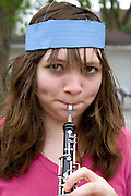 Oboe musician age 17 warming up for the long parade march. MayDay Parade and Festival. Minneapolis Minnesota USA