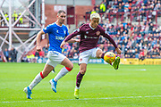 Ryotaro Meshino (#77) of Heart of Midlothian FC controls the ball ahead of Nikola Katic (#19) of Rangers FC during the Ladbrokes Scottish Premiership match between Heart of Midlothian and Rangers FC at Tynecastle Park, Edinburgh, Scotland on 20 October 2019.
