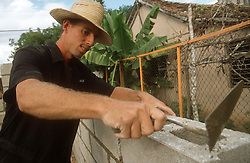 Builder cementing breeze block wall using trowel at Gibara; Cuba,