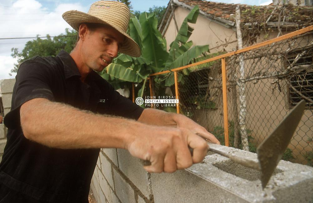 Builder cementing breeze block wall using trowel at Gibara; Cuba,