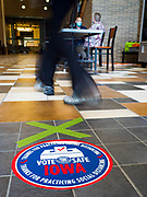 02 JUNE 2020 - WEST DES MOINES, IOWA: A person walks past a social distancing reminder and spot on the floor at a polling place on primary election day at Valley High School in West Des Moines. Because of the Coronavirus pandemic, all of the polling places in West Des Moines were consolidated to Valley High School, where voting booths were set up with social distancing in mind and booths were sanitized before they were reused. Although Iowa uses a caucus system to select presidential candidates, they use a primary election to select candidates for other offices. Statewide, the most watched race Tuesday is the Democratic Senate primary to select a candidate to run against Republican incumbent Joni Ernst.      PHOTO BY JACK KURTZ