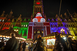 © Licensed to London News Pictures . Manchester , UK . Albert Square and Manchester Town Hall with people moving between Christmas Market stalls . FILE PHOTO DATED 10/12/2013 of Christmas Markets in Manchester as temperatures drop and 2014 seasonal markets start up across the country , selling mulled wine , german hot dogs , dutch pancakes , wooly hats and many other festive frivolities . Christmas markets provide an economic boost to many city centres and create a festive atmosphere on otherwise cold and dark nights . . Photo credit : Joel Goodman/LNP