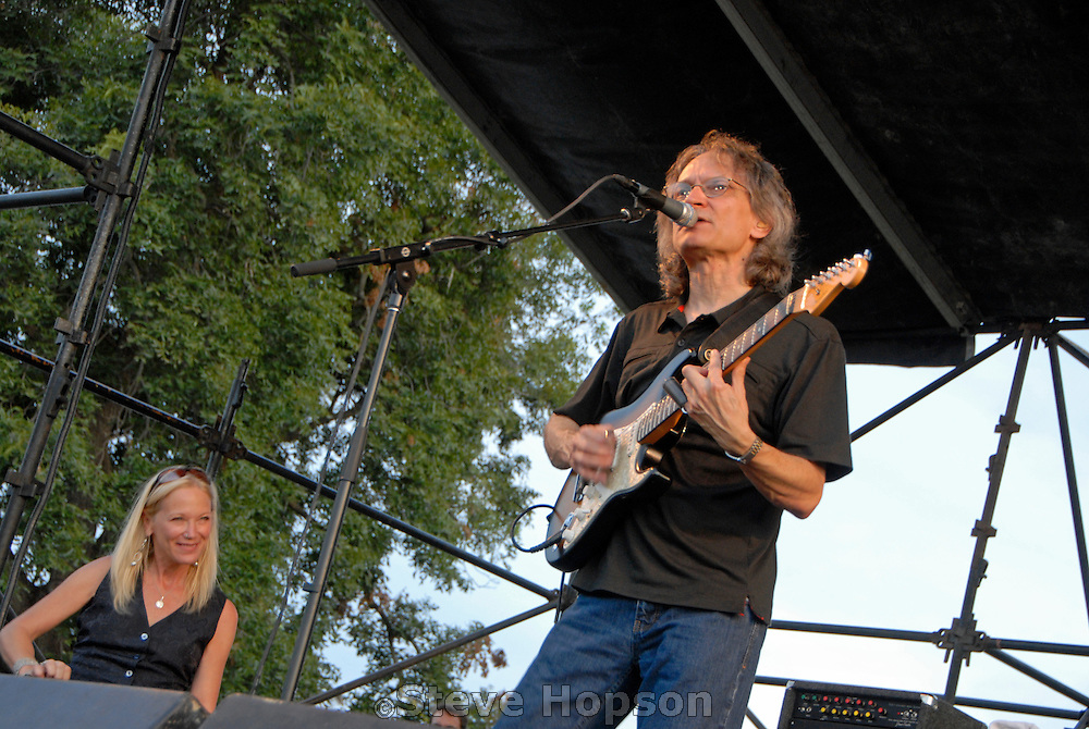 """Sonny Landreth and Cindy Cashdollar performing  at KGSR's Blues on the Green Series in Austin Texas, August 6, 2008. Sonny Landreth (born 1951) is an American blues musician from southwest Louisiana who is known as a slide guitar player. Eric Clapton has said Landreth is """"probably the most underestimated musician on the planet and also probably one of the most advanced."""" Cindy Cashdollar is a well known steel guitar player who has performed with Van Morrison, Bob Dylan and many other musicians."""