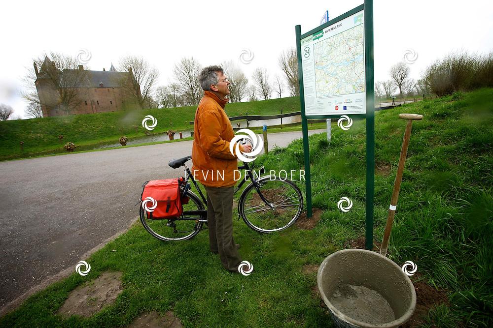 POEDEROOIJEN - Wilfried Romp heeft de nieuwe fietsknooppuntpaal bij Slot Loevestein geplaatst en in gebruik genomen. FOTO LEVIN DEN BOER - PERSFOTO.NU