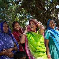 "Rajkumari Moira (centre in green) and other women take part in the AROH Mahila Kisan Manch (Women farmers federation) monthly meeting in Deramunshi village. Among other ideas, the group plan a march on the issue of land reform. Such meetings allow issues like cultivation techniques, accessing good quality seeds, qualifying for subsidized inputs and training. ..Rajkumari Moira, 45, from the Maurya caste, has four children, and lives in Deramunshi village. She is frustrated that women do all the domestic work and then labour on land for which they have no title, ""Women do all the household work; they bring up the children, take care of the family and do agricultural work as well. But if there is not joint entitlement to the land, it's a big risk. If the husband is good, then things are fine; but if he's a drunkard or there is a bad person, it's a high risk. And we don't have security of land or anything to help us."" She describes her own husband as a good man. On their one bigha (1,300 sq metre) of land, Rajkumari and her family grow vegetables like cauliflower, tomato, okra and potato, ..""Since we have only a small plot of land, we grow vegetables because we can sell them and get higher prices. We buy grains with the money. I can normally make about 10,000 rupees profit each year.  If we grew grains, we would earn about 6-7,000 rupees each year. ..In the north Indian state of UP (Uttar Pradesh), women are responsible for 70 to 80 percent of agricultural work but their contribution remains neglected at all the levels: family, social, economic and policy. Over three quarters of UP's households are involved in farming of which 91% percent operate on land that is marginal and small. Small and marginal farmers often lack access to major agricultural services, such as credit, extension, insurance, and markets...On October 15, 2005 a movement called AROH was launched campaigning for the recognition of women as farmers. A federation of women farmers popularly known as ""Aroah"