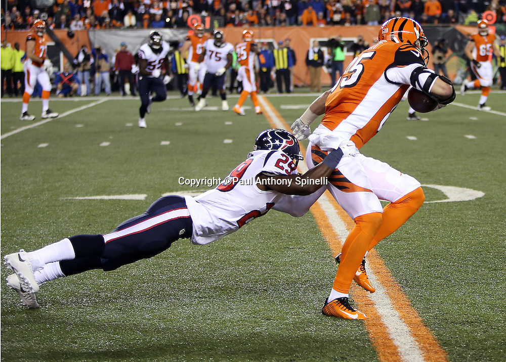 Cincinnati Bengals tight end Tyler Eifert (85) gets tackled by diving Houston Texans strong safety Andre Hal (29) as he catches a pass for a fourth quarter gain of 6 yards during the 2015 week 10 regular season NFL football game against the Houston Texans on Monday, Nov. 16, 2015 in Cincinnati. The Texans won the game 10-6. (©Paul Anthony Spinelli)