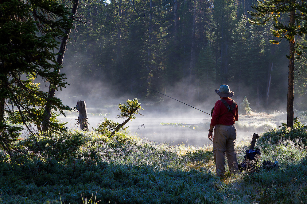 A fly fisherman prepares and studies the water of a Utah backcountry lake as the early morning mist comes off the water.
