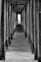 Grungy view underneath the Huntington Beach pier in California, noise and black and white added to complete the effect.