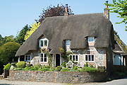 Typical English stone built thatched cottage brick and flint construction, roof thatching, chimneys in Ramsbury, Wiltshire, UK