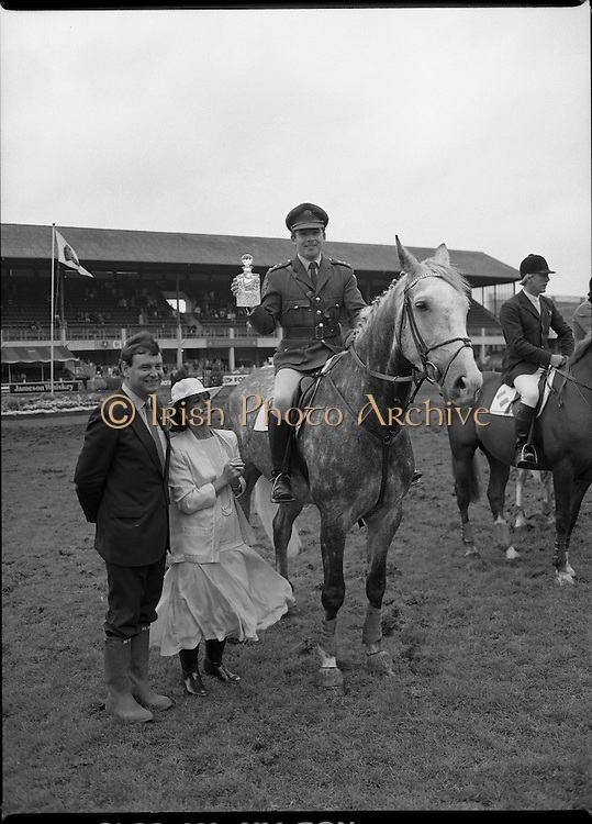 Jameson Whiskey International at the Dublin Horse Show.  (R39).1986..07.08.1986..08.07.1986..7th August 1986..The Jameson Whiskey International at the Dublin Horse Show in the RDS was won by Peter Charles of Great Britain. He rode 'Merrimandias' to victory in the event...Image shows Capt Gerry Mullins with the trophy presented to him by Mrs Marie Cummins, wife of the Managing Director, Irish Distillers. Capt Mullins the Irish Whiskey Jameson's, Irish, Whiskey, jameson,Classic aboard 'Glendalough'. Mr Michael Cummins also features in the picture.