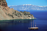A sailboat cruises into the harbor on Thirasia Island (or Therasia), Greece. Across the submerged caldera is Santorini Island. Geologic and human history of Santorini: Humans first arrived around 3000 BC on this volcano known in ancient times as Thira (or Thera). The island was a volcanic cone with a circular shoreline until 1646 BC, when one of earths most violent explosions blasted ash all over the Mediterranean, sunk the center of the island, launched tidal waves, and may have ruined the Minoan civilization 70 miles away on Crete. Remarkably, volcanic ash dumped onto the volcanos flanks actually preserved the village of Akrotiri and its 3600-year-old frescoes from the Minoan era. These are some of the earliest known examples of world art history, which you can now view in museums. In 286 BC, the volcano split off Thirasia (Little Thira) Island (to the West). The volcano began rebuilding, and in 197 BC the small center islet of Palia Kameni appeared. In 1707 CE, lava started forming Nea Kameni, the larger center island which erupted as recently as 1956 and caused a huge earthquake (7.8 on the Richter scale) which destroyed most of the houses in the towns of Fira and Oia. Fira and Oia have since been rebuilt as multi-level mazes of fascinating whitewashed architecture, attracting tourists from around the world.