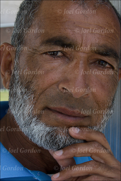 Head and shoulder portrait of Pakistani American male with white beard making eye contact with camera. He has a questioning look in this eyes and body language.