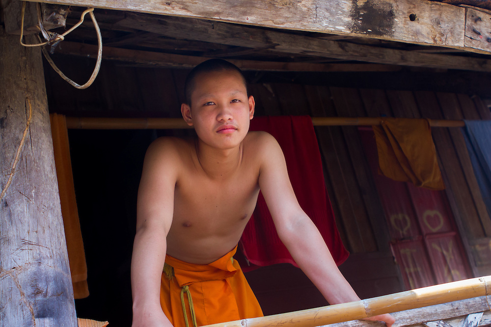 A young monk on the balcony of his home at Wat Mounea, one of the many buddhist monasteries of Luang Prabang.<br />