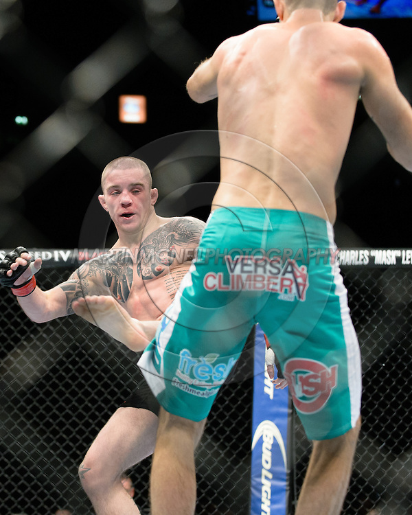 """MANCHESTER, ENGLAND, OCTOBER 26, 2013: Cole Miller (green shorts) and Andy Ogle (black trunks) compete during """"UFC Fight Night 30: Machida vs. Munoz"""" inside Phones4U Arena in Manchester, England (© Martin McNeil)"""