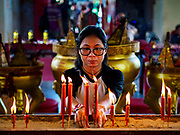 04 SEPTEMBER 2017 - BANGKOK, THAILAND: A woman lights prayer candles at Chaomae Thapthim Shrine before a food distribution event at the shrine. About 1,000 people came to the shrine for the annual food distribution. Staples, like rice and cooking oil, are donated to the shrine throughout the year and donated to poor people from the communities around the shrine. Food distributions like this are a tradition at Chinese shrines in Bangkok and a common way of making merit for the people who donate the staples.     PHOTO BY JACK KURTZ