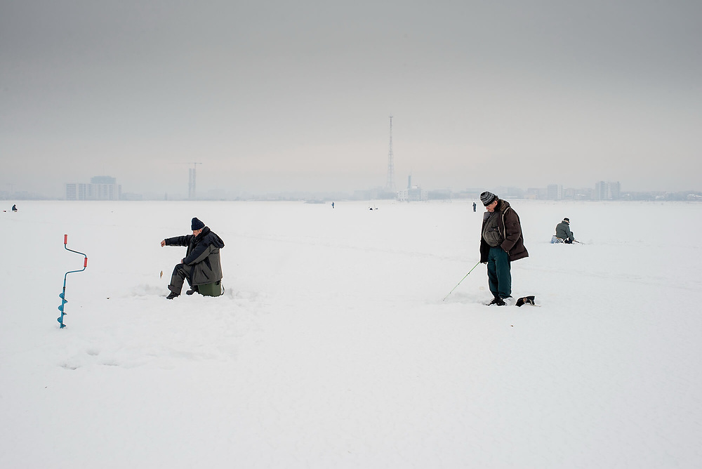 People ice fishing on the frozen surface of Lacul Morii, a large artificial lake built during the communist-era in the 1980s to protect the city against floods.