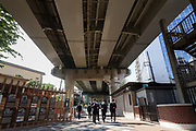 Japanese school boys walk under an overpass of the  Shouto Expressway in Edogawabashi, Tokyo, Japan Friday April 20th 2018